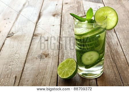 Water with lime and cucumber against wood