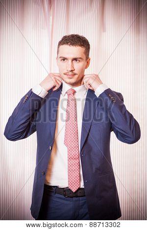 A Man Adjusts His Tie