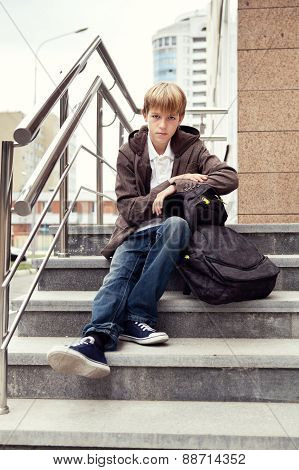 Serious Boy Sitting On Stairs. Outdoor