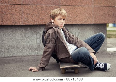 School Teen Sits On Skateboard Near School