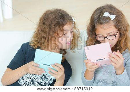 Two young sisters playing video gales
