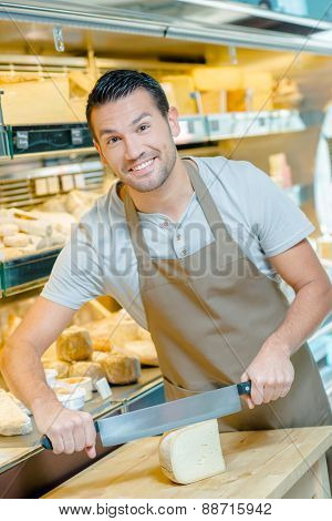 Local deli worker slicing some cheese