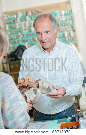 Cobbler explaining what needs to be done to a shoe