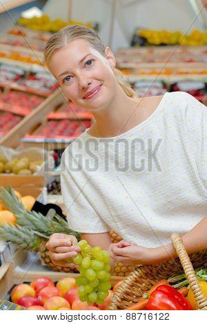 Woman choosing a bunch of grapes