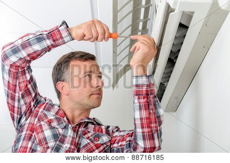 Man repairing his air conditioning system
