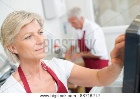 Woman using a touch screen till system