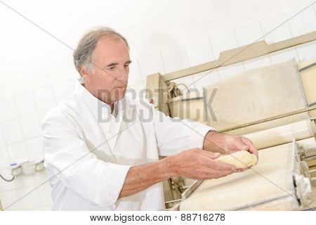 Baker preparing baguettes for the oven