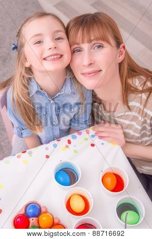 mother with child at room with colorful easter eggs