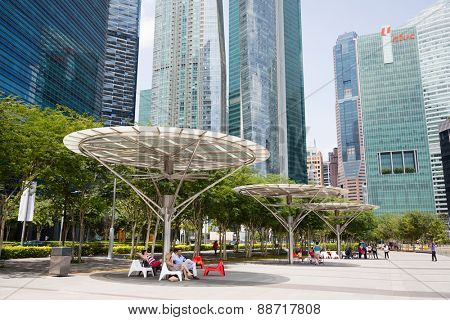 SINGAPORE - FEBRUARY 18, 2015: People relax in the shade under umbrellas on the waterfront Marina Bay. Quay Marina Bay a popular holiday destination and hanging out with locals and tourists.
