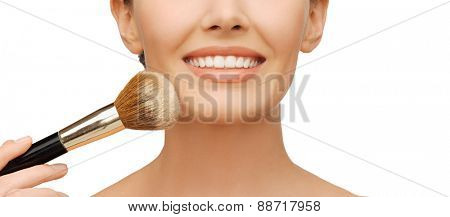 beauty and makeup concept - woman applying powder foundation with brush