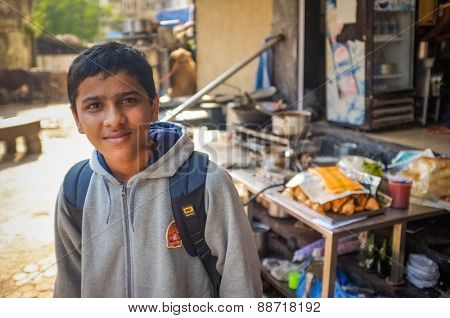 MUMBAI, INDIA - 09 JANUARY 2015: Indian school boy in front of shop.