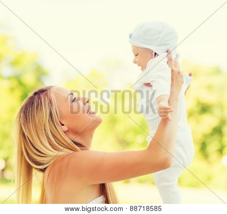 family, child and parenthood concept - happy mother holding little baby in park
