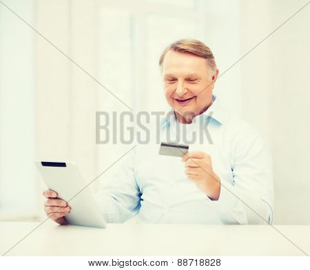 business, oldness, online banking, internet shopping and oldness concept - smiling old man with tablet pc and credit card at home