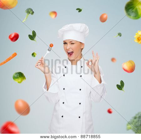 cooking and food concept - smiling female chef, cook or baker with fork and tomato showing ok sign over falling vegetables on gray background