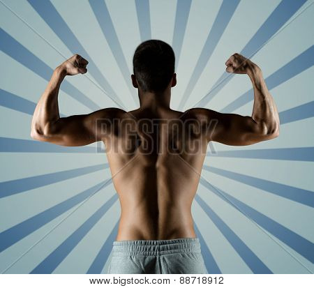 sport, fitness, bodybuilding, strength and people concept - young man or bodybuilder showing biceps over blue burst rays background