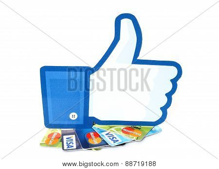 KIEV UKRAINE - MARCH 21 2015: Facebook thumbs up sign printed on paper and placed on cards Visa and