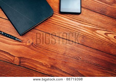 smartphone and notebook on wooden table