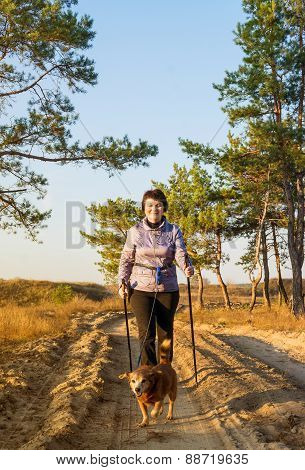 Woman With Sticks For Walking And Dog On Walk