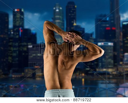 sport, fitness, bodybuilding, strength and people concept - young man or bodybuilder showing muscles over night city background from back