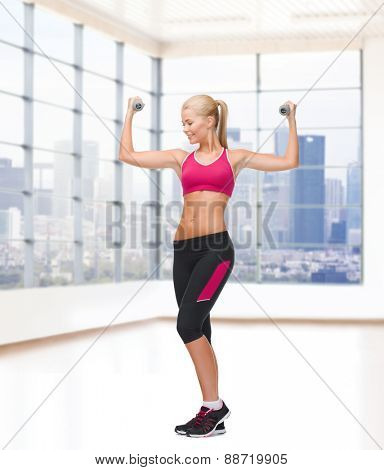 sport, fitness, training, weightlifting and people concept - young sporty woman with dumbbells flexing biceps over gym background