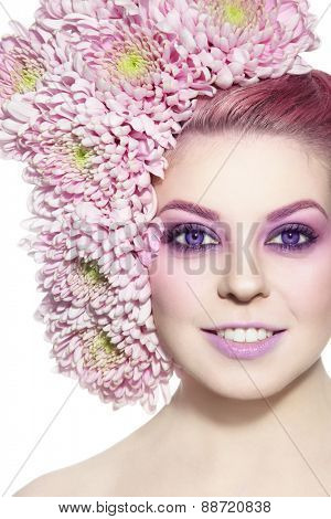 Portrait of young beautiful smiling woman with stylish violet make-up and flowers in her hair over white background