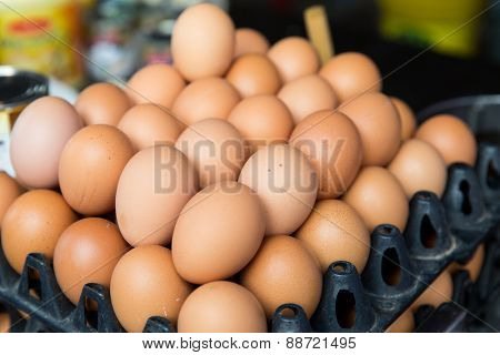cooking, asian kitchen, sale and food concept - fresh eggs on tray at asian street market