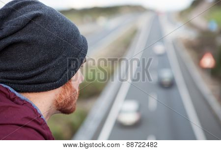 Cool man back at the top of a bridge over a highway