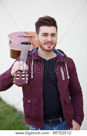 Handsome cool man carrying a guitar on his shoulders