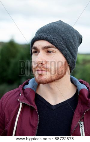 Handsome cool man with cap wool smiling outside