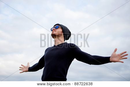 Cool handsome guy with his arms extended with the sky of background