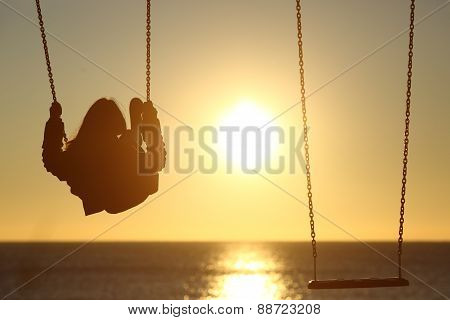 Lonely Woman Silhouette Swinging At Sunset On The Beach
