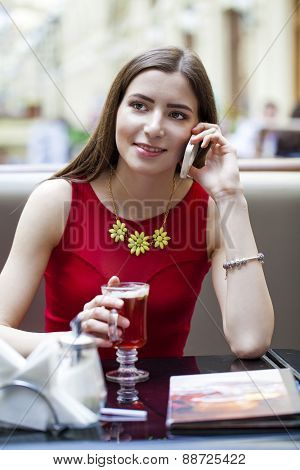 Young beautiful brunette girl sitting in a coffee shop and calling by phone