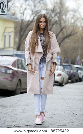 Young beautiful woman in beige coat and torn jeans and pink sneakers on spring street