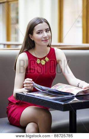 Young beautiful girl sitting in a cafe and considers the menu