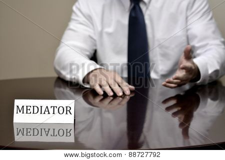 Man at desk with folded hands business card for Mediator to talk and help people