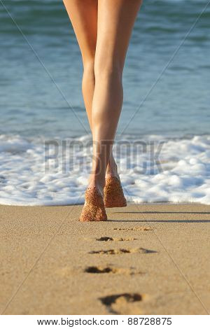 Woman Legs Walking On The Sand Of The Beach Towards The Sea