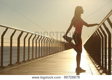 Woman Silhouette Exercising Stretching On A Bridge