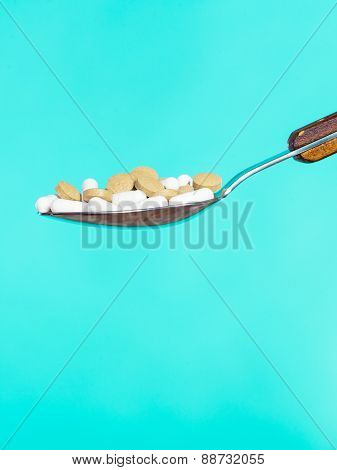 Spoon With Pills On Blue