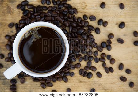 Coffee beans background on wooden, Fresh coffee beans with coffee cup on wooden background, Drinking