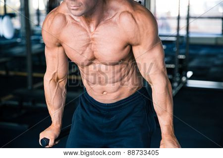 CLoseup portrait of a man workout on bars in gym