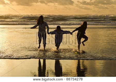 Family runs in the surf at sunset.