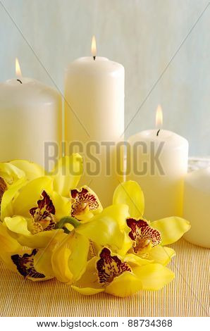 Spa composition (candle and yellow orchids on towel)