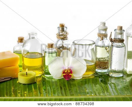 spa supplies with orchid, candle,soap, bottle oil on banana leaf