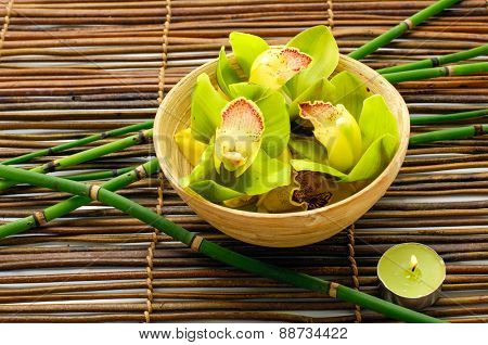 Wooden bowl of orchid with grove ,candle,on bamboo mat