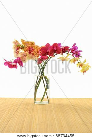Set of bouquet of orchids in vase. on mat