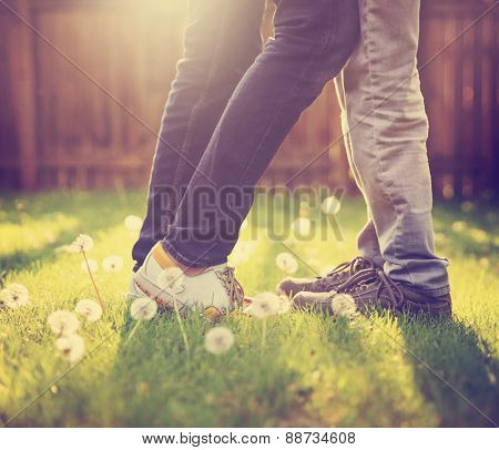 young couple kissing in a backyard in summer sun light at sunset with dandelions blooming toned with a retro vintage instagram filter app or action effect (very shallow depth of field - on the shoes)