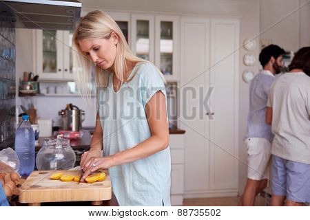 young woman carefully cutting fresh lemon at a friends gathering in kitchen at home