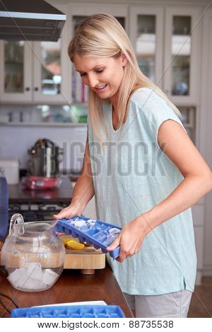Young woman shaking the ice tray to fill jug in kitchen at home