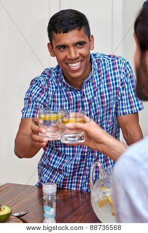 young cheerful man toasting with friends indoors at gathering