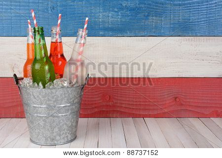 A bucket of soda bottles with drinking straws against a red, white and blue background for a 4th of July picnic, with copy space.